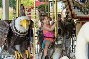little girl enjoying a ride on the endangered species carousel