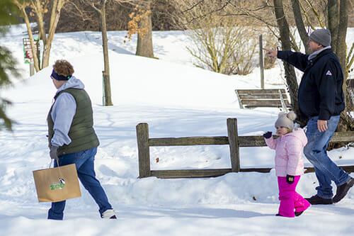 family walking through snow at the zoo